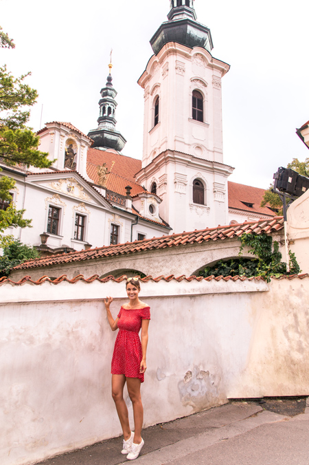 a girl in a red dress standing in front of church in Prague, best photo spot