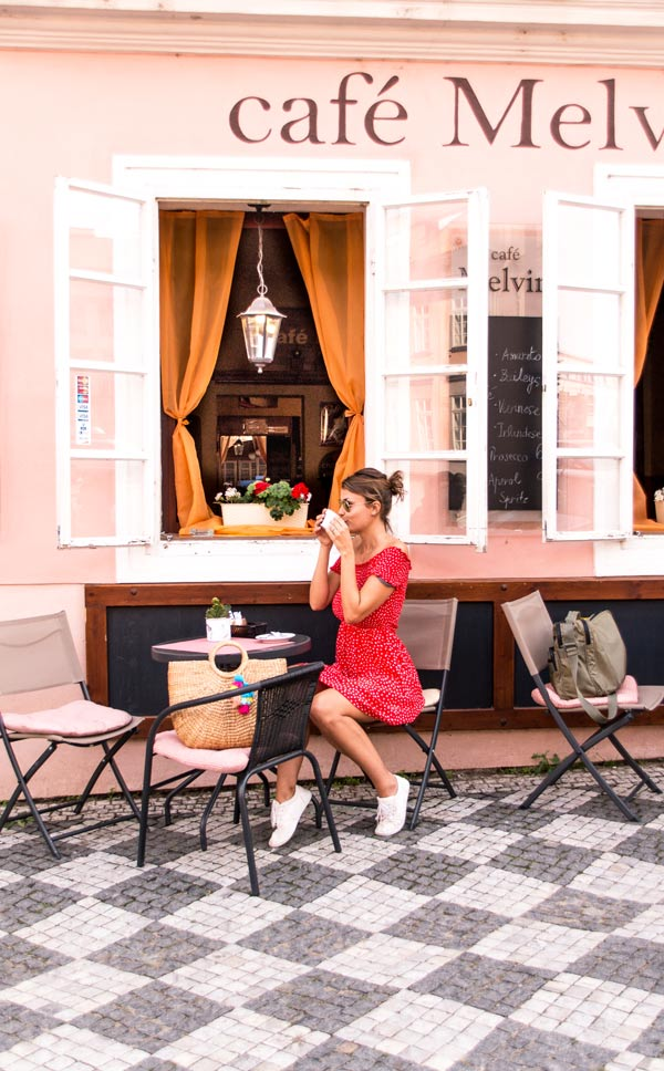 woman in red dress siting and drinking coffee in front of pink building