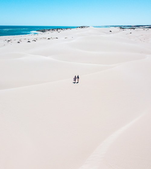 two people holding hands in the middle of white sand dunes in Warroora station