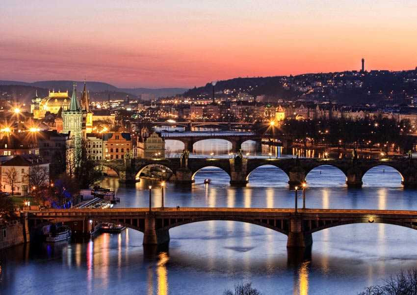 orange sky, bridges and the view on night Prague with lights