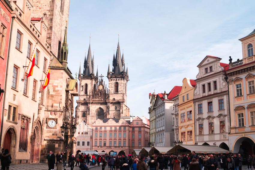 a view on the two tower tower with colourful buildings and many people around in old town square of Prague