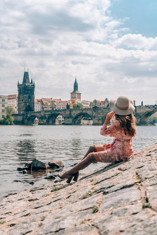 woman in red dress and white hat sitting on stones with a view on the Charles bridge