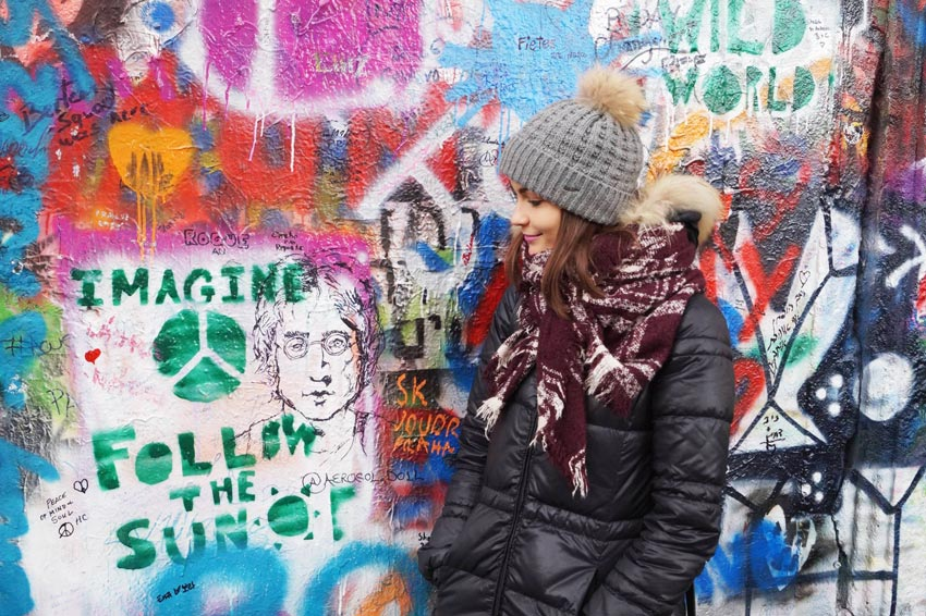 woman in grey hat, black jacket in front of the colourful Joh Lenon Wall in Prague