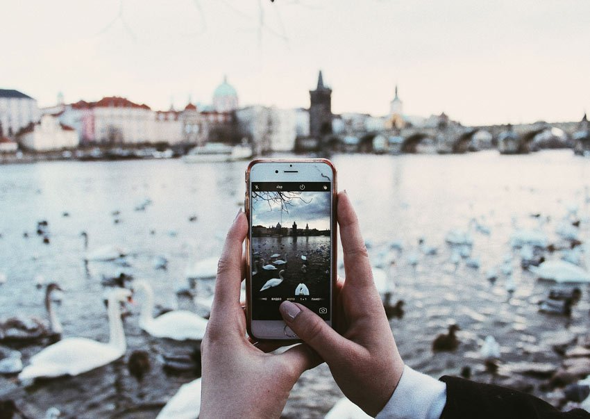 shot of hand holding a phone with a view on the river and Charles bridge with swans around