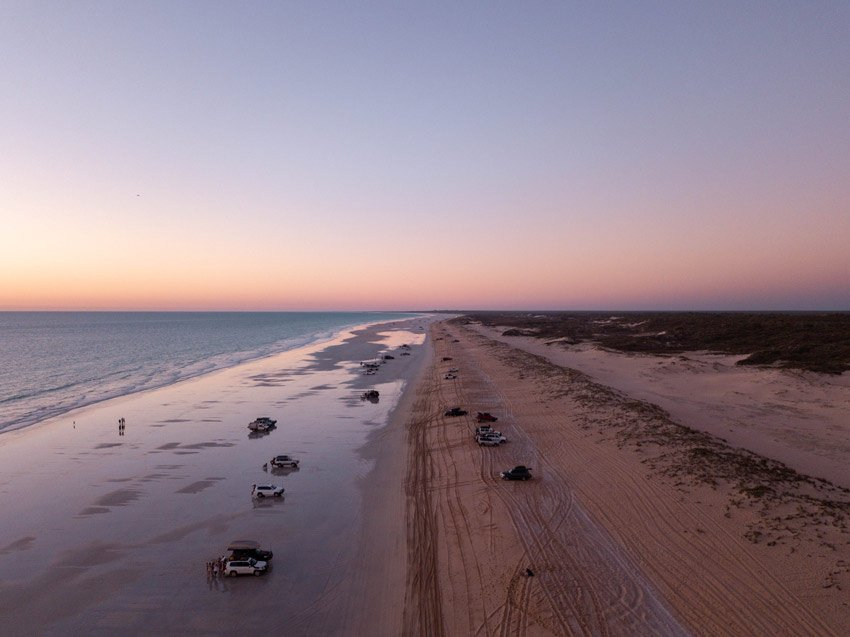 purple pink sky over the beach with cars standing