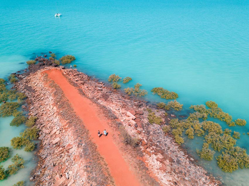 arial drone shot with red beach,two people blue water and green mangroves, one of the best things to see in Broome