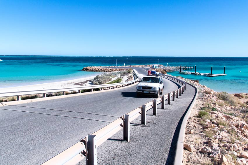 white car driving on the grey road surrounded by blue water