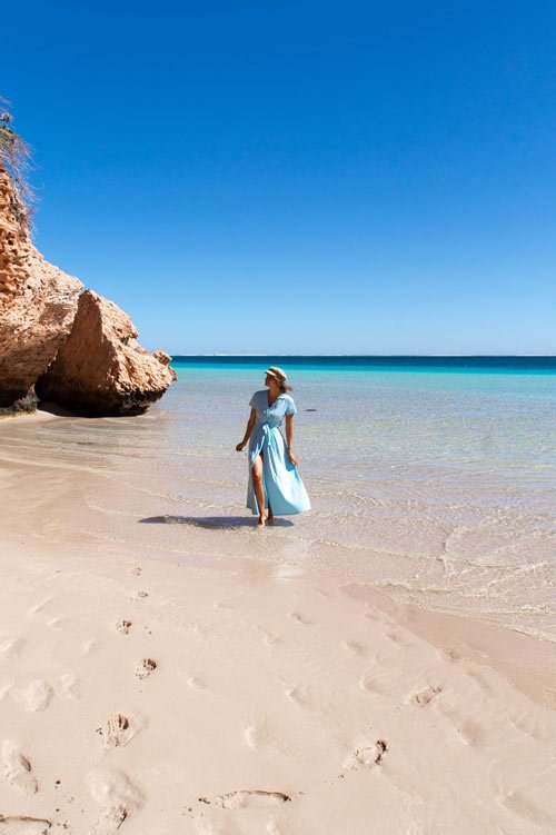 woman in a blue dress posing near brown cliff on the beach in Coral bay in Western Australia