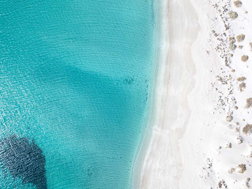 arial shot of white sand beach with blue water near Coral bay, Australia