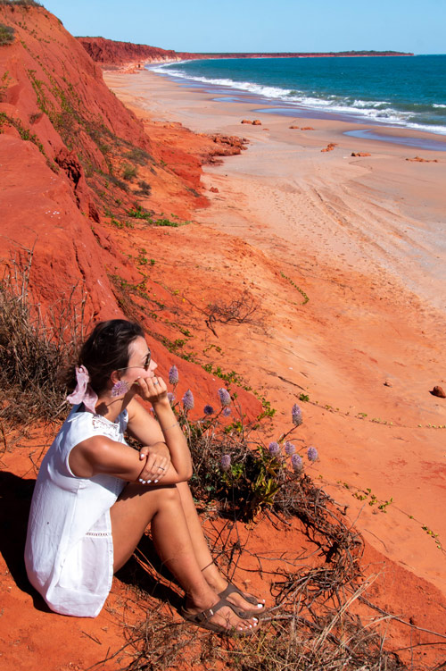 woman in a white dress sitting on the red cliff next to blue water