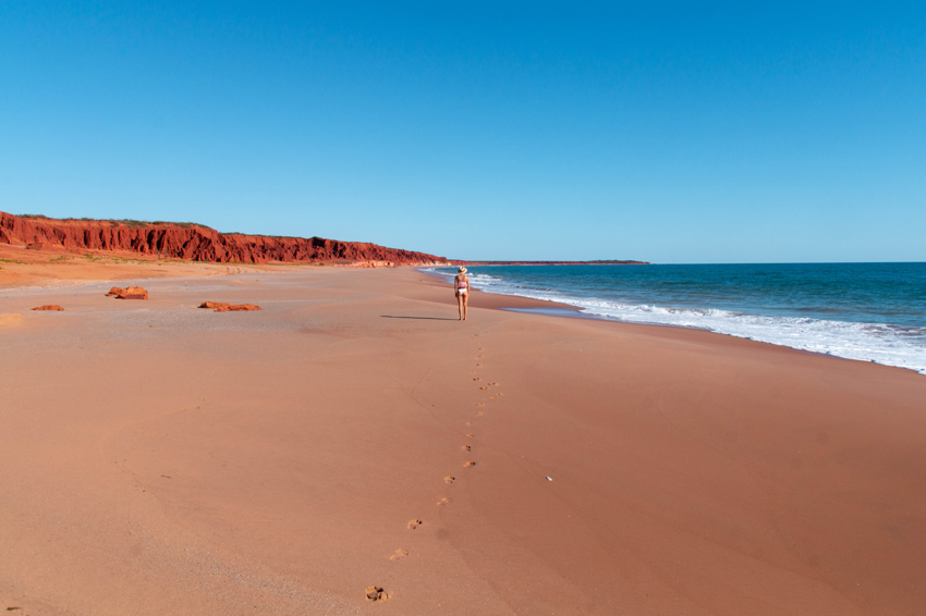 woman walking on the red sand beach next to blue water, perfect trip from Broome