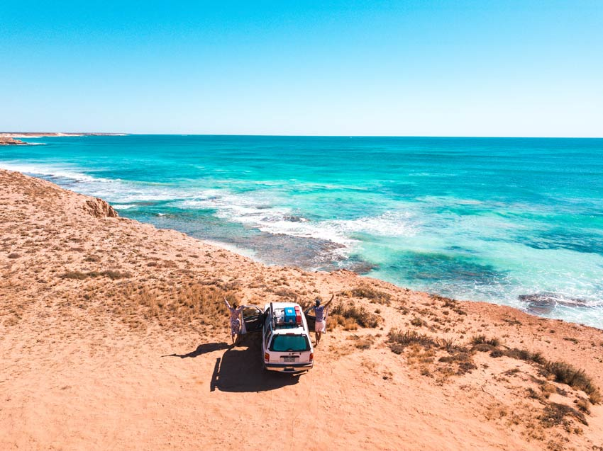 two people popping out from a white car and looking out on the ocean in Warroora station, WA