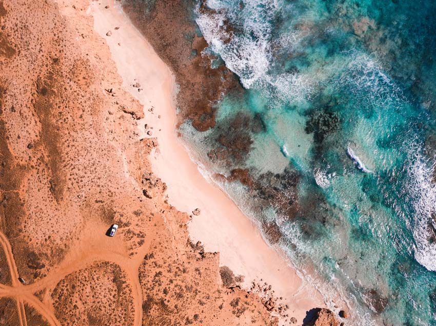 drone photo, white car standing on a brown soil and view on the beach and the ocean in Warroora